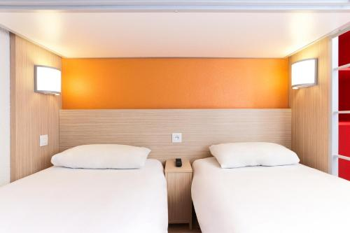 A bed or beds in a room at Premiere Classe Herblay