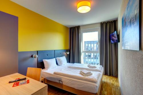 A bed or beds in a room at MEININGER Hotel Frankfurt/Main Messe