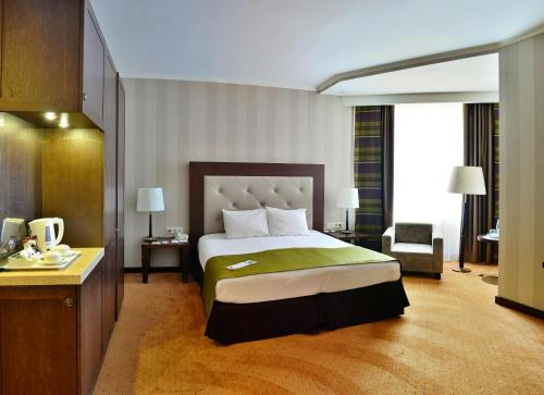 A bed or beds in a room at Petro Palace Hotel
