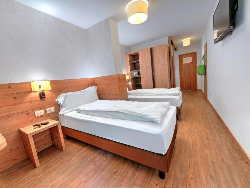 A bed or beds in a room at Luna Wellness Hotel