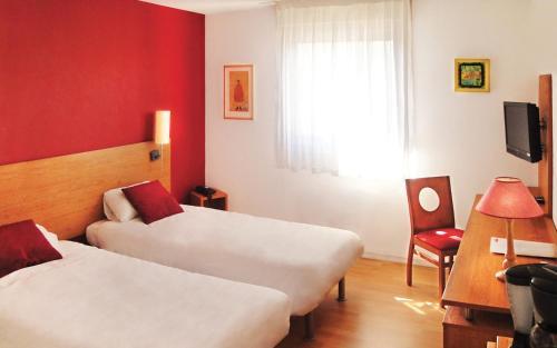 A bed or beds in a room at Séjours & Affaires Bordeaux de L'Yser
