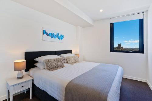 A bed or beds in a room at Beau Monde Apartments Newcastle - Horizon Newcastle Beach