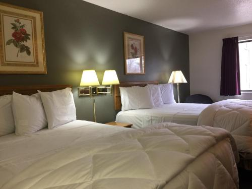 A bed or beds in a room at Amerihost Inn & Suites - Mexico