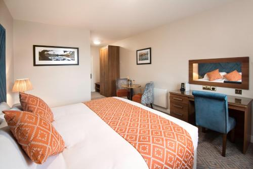 A bed or beds in a room at The Ripley Court Hotel