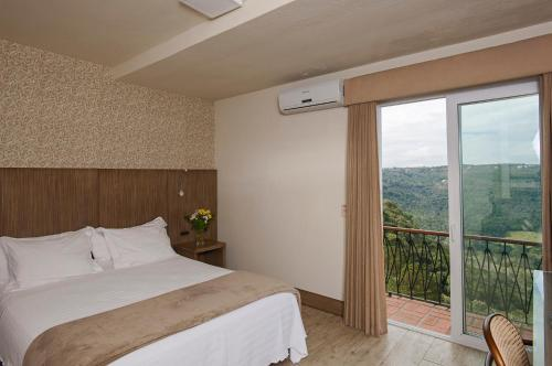 A bed or beds in a room at Villa Bella Hotel
