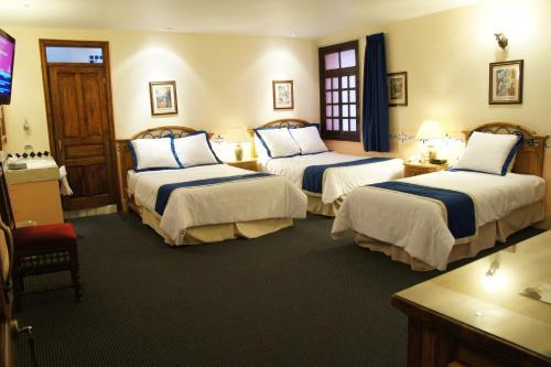 A bed or beds in a room at Posada Santa Fe