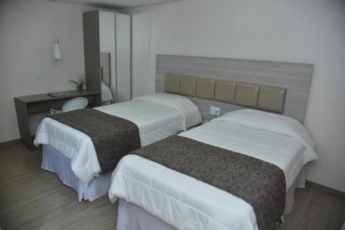 A bed or beds in a room at Hotel Village Confort Campina Grande