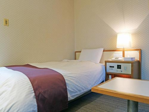 A bed or beds in a room at Hotel Takeshi Sanso