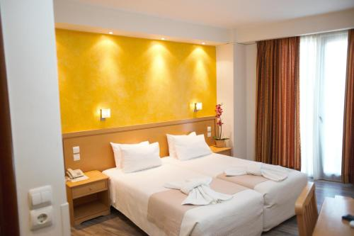 A bed or beds in a room at Athens Golden City Hotel