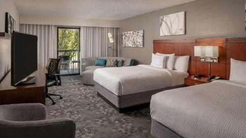 A bed or beds in a room at Courtyard Baton Rouge Siegen Lane