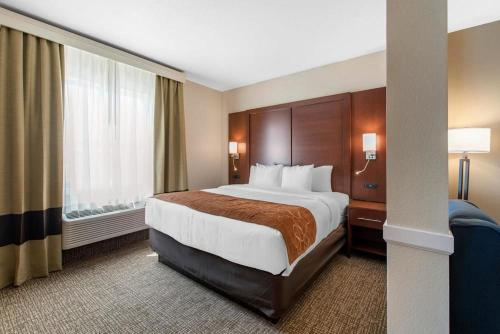 A bed or beds in a room at Comfort Suites Denver International Airport