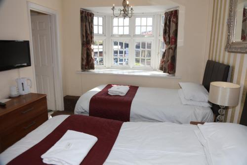 A bed or beds in a room at The Half Moon Inn