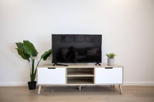 A television and/or entertainment center at Executive Luxury Apt with parking next to Station