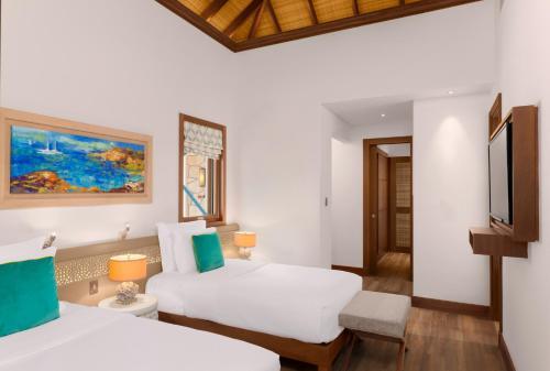 سرير أو أسرّة في غرفة في منتجع جزيرة البنانا الدوحة بإدارة أنانتارا
