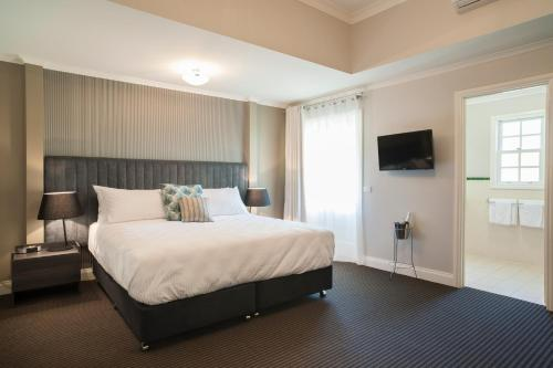A bed or beds in a room at Oscar's On The Yarra