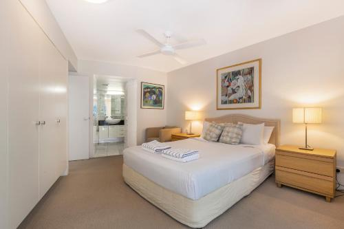 A bed or beds in a room at The Cove Noosa