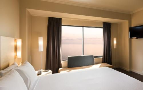 A bed or beds in a room at Stamford Grand Adelaide