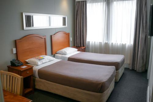 A bed or beds in a room at Great Southern Hotel Sydney
