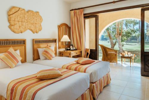 A bed or beds in a room at Mercure Luxor Karnak