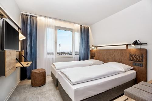 A bed or beds in a room at H2 Hotel München Olympiapark