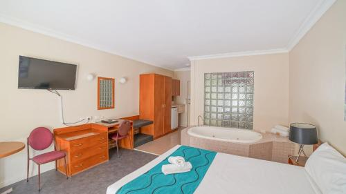 A television and/or entertainment center at Country 2 Coast Motor Inn Coffs Harbour