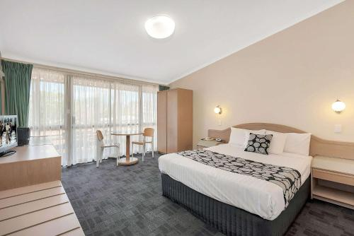 A bed or beds in a room at Econo Lodge Toowoomba Motel & Events Centre