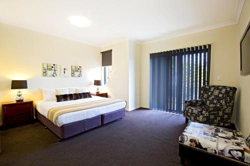 A bed or beds in a room at Astina Serviced Apartments - Central