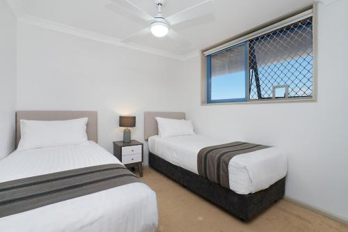 A bed or beds in a room at Newcastle Short Stay Apartments - Sandbar Newcastle Beach