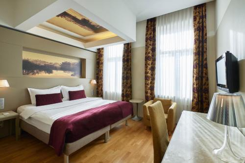 A bed or beds in a room at Opera Hotel