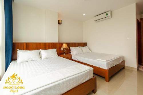 A bed or beds in a room at Ngoc Long Sam Son Hotel