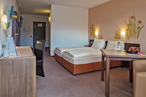 A bed or beds in a room at Hotelpark der Westerwald Treff