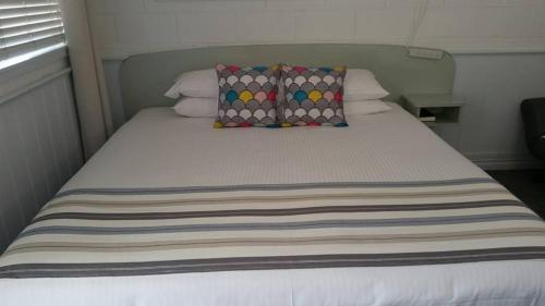 A bed or beds in a room at Arcadia Motel