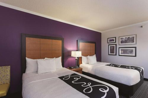 A bed or beds in a room at La Quinta by Wyndham Baton Rouge Siegen Lane