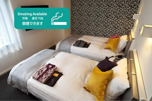 A bed or beds in a room at Fukuyama Oriental Hotel