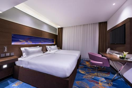 A bed or beds in a room at Novotel Beijing Peace
