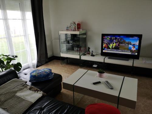 A television and/or entertainment center at Maison d'hôtes à Montévrain