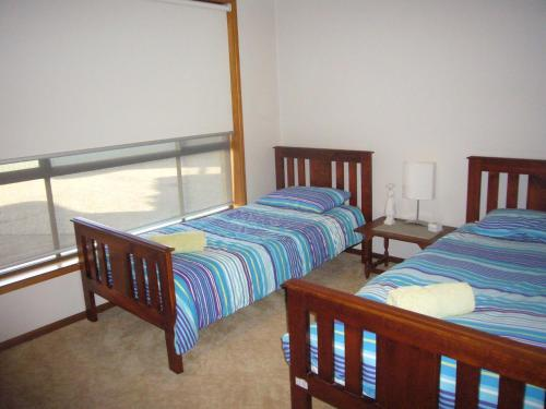 A bed or beds in a room at Sunnyside - Sawtell, NSW