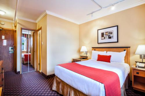 A bed or beds in a room at Howard Johnson by Wyndham Vancouver Downtown