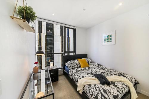 A bed or beds in a room at A Modern & Cozy 2BR CBD Apt Near Melbourne Central