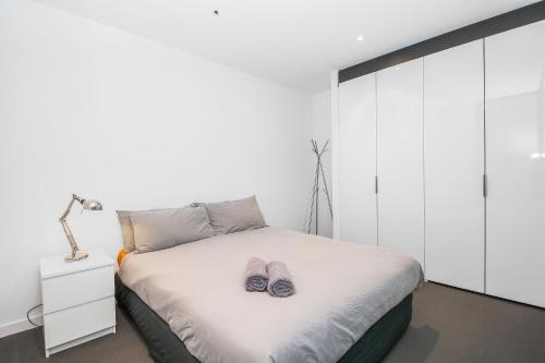 A bed or beds in a room at A Cozy CBD Suite Near Southern Cross + Pool & Gym