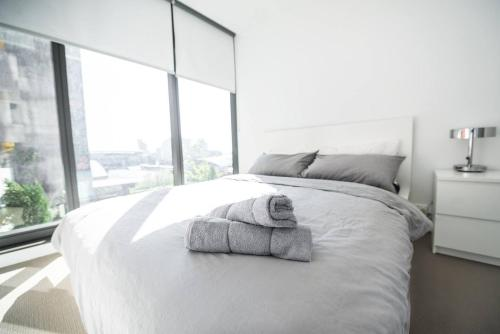 A bed or beds in a room at Contempo CBD Suites with Pool, Gym + FREE WiFi