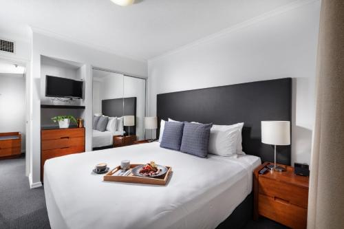 A bed or beds in a room at The Sebel Brisbane