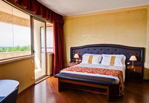 A bed or beds in a room at Galileo Palace Hotel