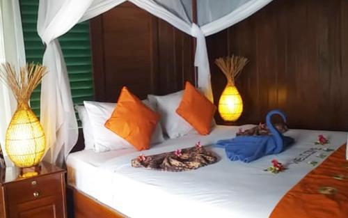 Uma cama ou camas num quarto em Bastianos Lembeh Dive Resort