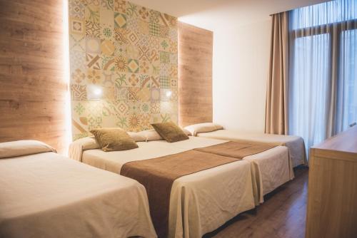 A bed or beds in a room at Hostal Marenostrum
