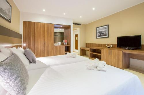 A bed or beds in a room at Dolmen Hotel Malta