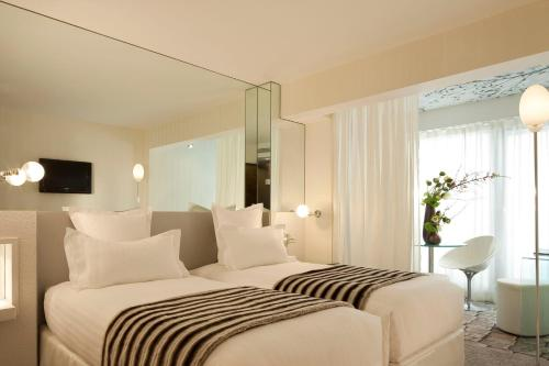 A bed or beds in a room at Le 7 Eiffel Hotel