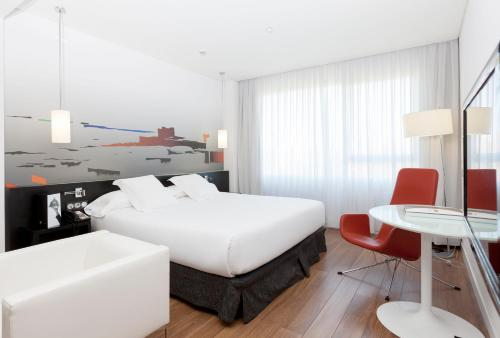 A bed or beds in a room at Axor Barajas