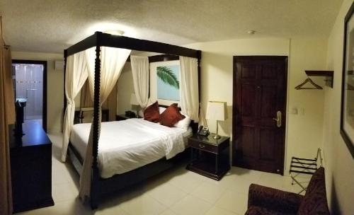 A bed or beds in a room at Villa Elegance Hotel & Apartment