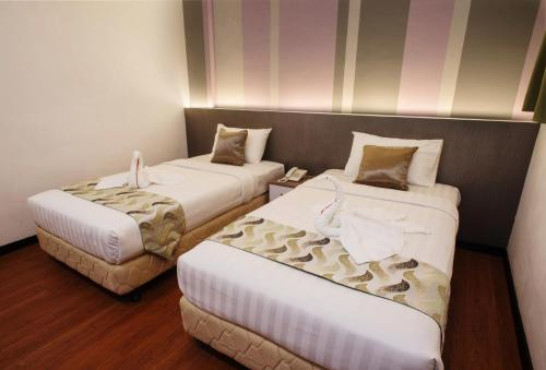 A bed or beds in a room at Heliconia hotel